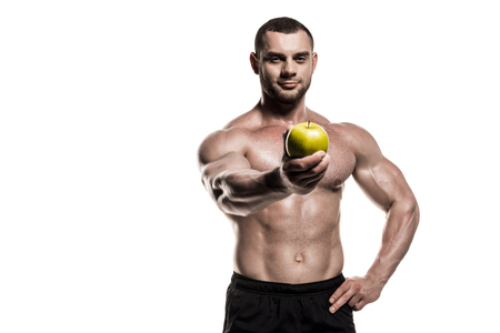 shirtless muscular sportsman presenting apple isolated on white