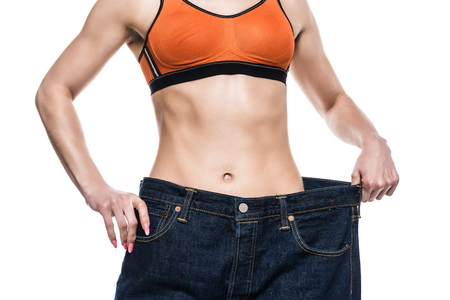 cropped view of sportswoman wearing oversized jeans to show her slim body