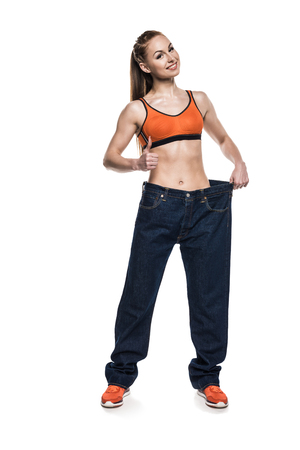sportswoman wearing oversized jeans to show her slim body while showing thumb up Stock fotó