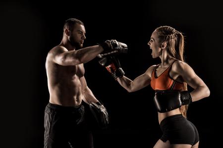 Sportieve gespierde jonge man en vrouw samen boksen