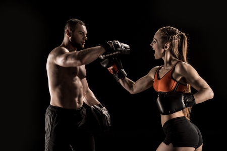 Sporty muscular young man and woman boxing together