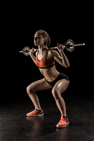 young sportswoman lifting barbell and looking away