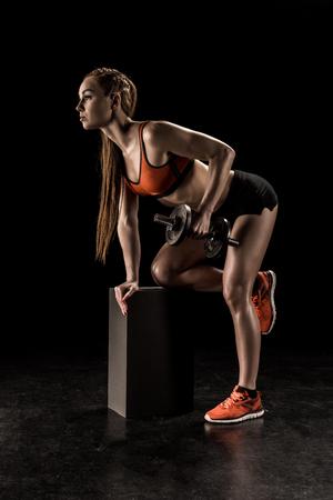筋肉の若いスポーツ選手の膝の上に立って、ダンベル運動