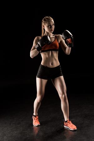 jonge sportvrouw in bokshandschoenen training en wegkijken