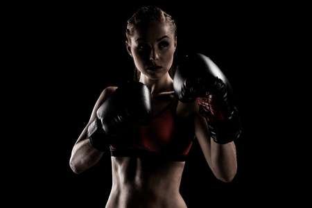 caucasian muscular sportswoman exercising in boxing gloves