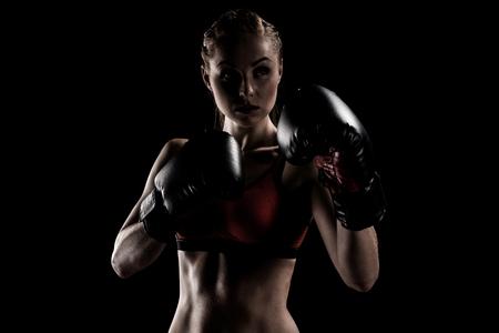 Kaukasische gespierde sportvrouw te oefenen in bokshandschoenen