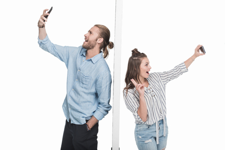 Excited young couple taking selfie with smartphones while standing separated by wall Reklamní fotografie