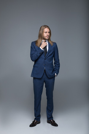 handsome long haired man wearing stylish suit and looking away