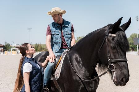 그의 여자 친구에 손을 잡고 말을 타고 앉아 카우보이 모자에 남자 스톡 콘텐츠