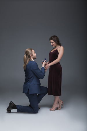 man in tuxedo making marriage proposal to his girlfriend while standing on one knee