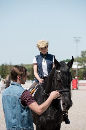 고삐를 들고 남자가 말을 타고 앉아 카우보이 모자에 여자