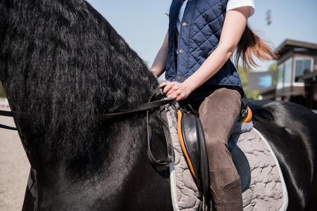 야외에서 검은 말을 타는 젊은 여성