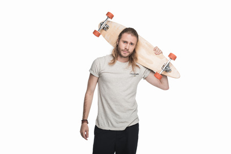 young skeptical man holding longboard and looking at camera Stock Photo