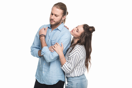 young woman touching serious young man standing and looking away