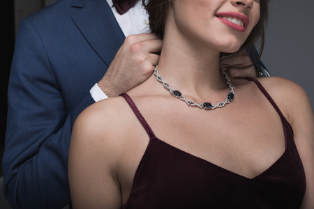 man in tuxedo putting necklace on his girlfriend