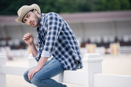 cowboy beard: young man in cowboy hat sitting on wooden fence and looking at camera Stock Photo