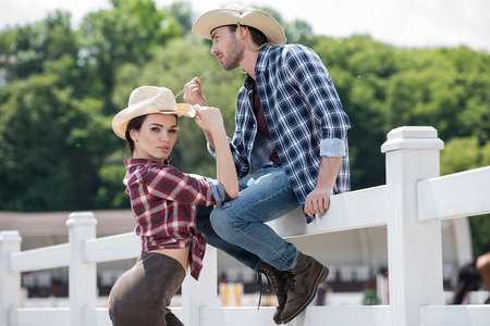 cowboy style couple posing together on ranch