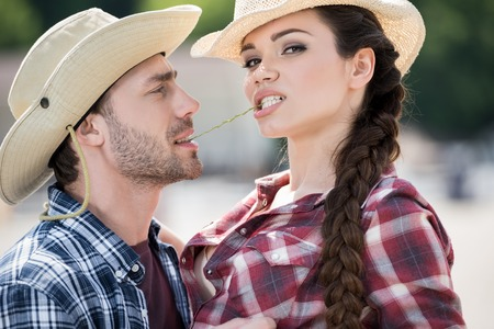 passionate cowboy style couple embracing with straw