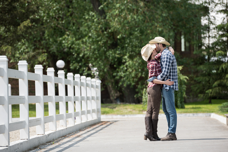 couple kissing while spending time in park at daytime