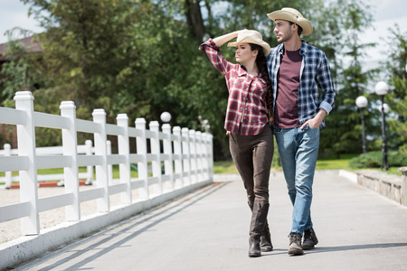 cowboy with his girlfriend walking on pathway in park at daytime Stock Photo