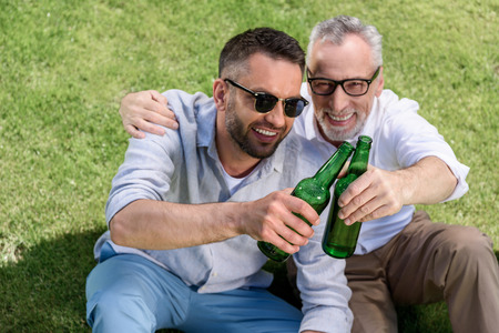 sitting father and adult son clinking with beer bottles