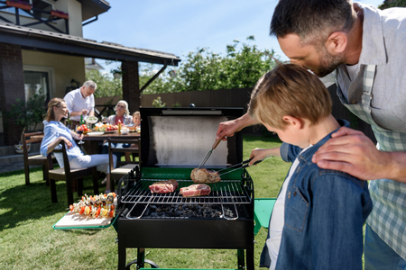 father and son grilling meat while family sitting at table outdoors