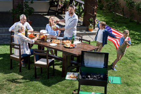 family having barbecue while celebrating 4th july together
