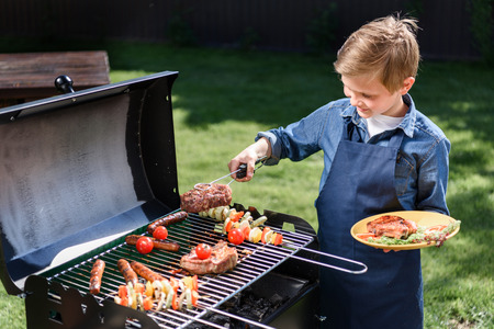kid boy in apron preparing tasty stakes on barbecue grill outdoors