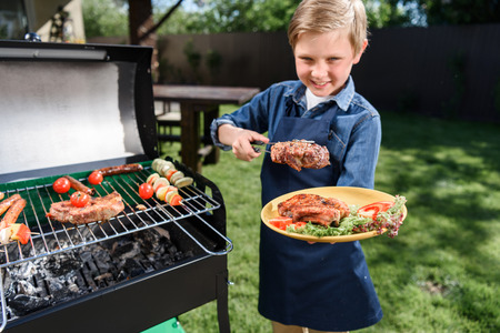 stakes: kid boy in apron preparing tasty stakes on barbecue grill outdoors