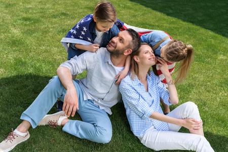 米国旗と草の上に座って幸せな家族