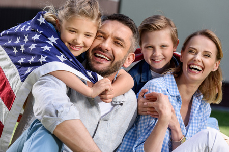 Happy family with american flag hugging outdoors Stock Photo