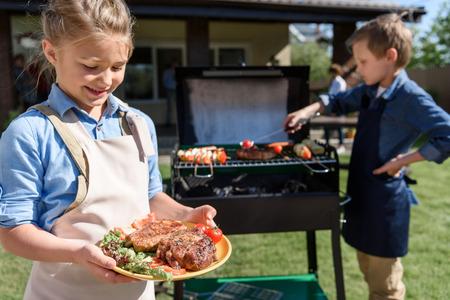 fille dans le tablier tenant plaque avec des steaks frais tout en faisant son frère de la viande sur le gril