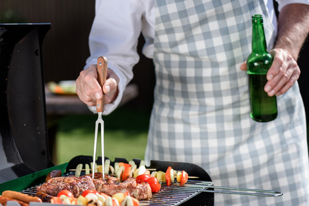 man preparing meat and vegetables on grill and drinking beer from bottle Stock Photo