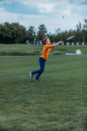 boy playing badminton with racquet and shuttlecock, on green field