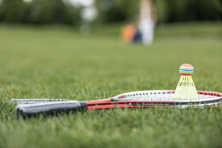 two badminton racquets and shuttlecock on green grass