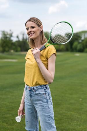 よそ見しながらバドミントン ラケットと羽根で立っている金髪の女の子 写真素材