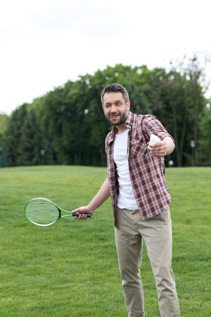 man sticking tongue out during play badminton game in park, summertime concept