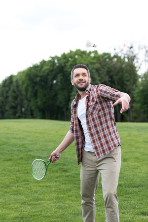active man playing badminton game in park, summertime concept Stock Photo