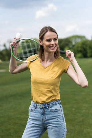shuttlecock: woman posing with badminton racquet and shuttlecock while looking away Stock Photo