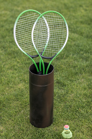 badminton racquets in container and shuttlecock on green grass Фото со стока