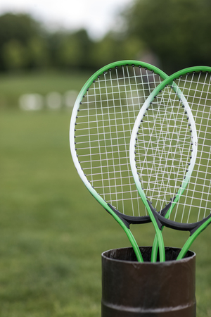 two badminton racquets in container outdoors