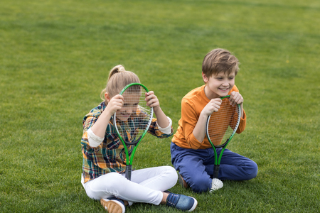 shuttlecock: brother and sister with badminton racquets sitting on green field