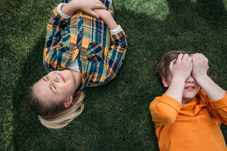 adorable kids sunbathing while lying on grass