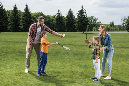 Parents teaching little kids how to play badminton