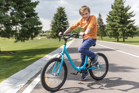 casual kid boy riding bicycle in park at daytime