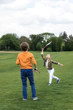 broer en zus spelen badminton op groen gras