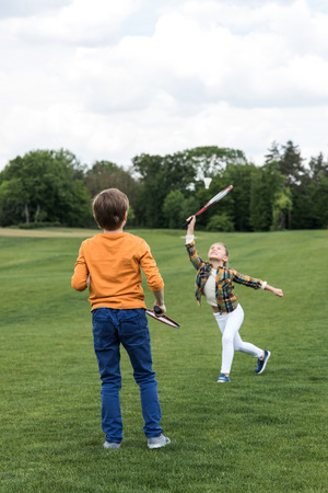brother and sister playing badminton on green grass