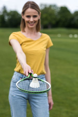shuttlecock: woman holding badminton racquet with shuttlecock on the top
