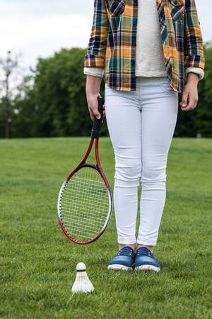 little girl holding badminton racquet and standing on green grass with shuttlecock
