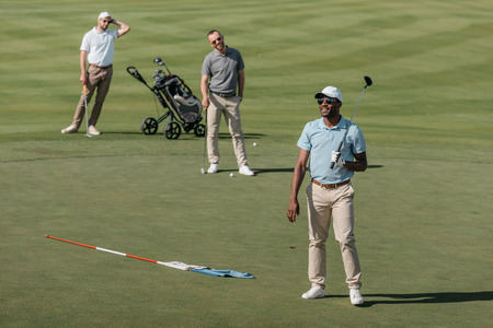 multiethnic sportsmen standing with golf clubs on green pitch